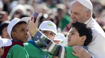 Foto di papa Francesco con fanciulli e smartphone
